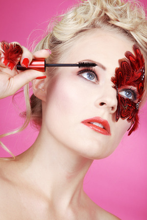 Beautiful face with red feathers and a mascara photo