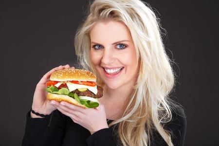 beautiful model presents a Burger with cheese Archivio Fotografico