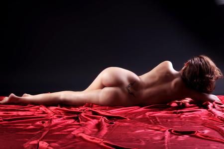 desnudo artistico: mujer desnuda acostada en el piso rojo