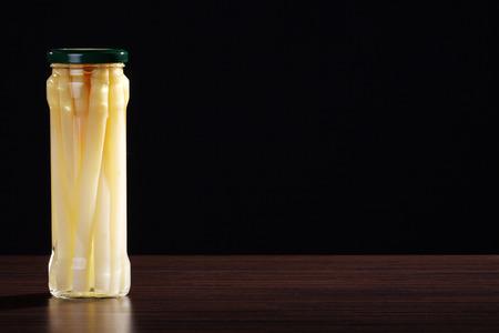 asparagus: asparagus in glass jar on brown table Stock Photo