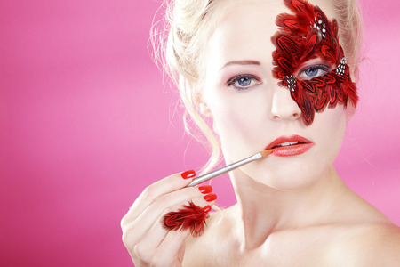 Beautiful face with red feathers and a lip brush photo
