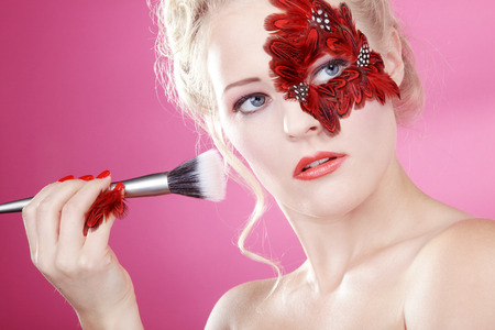 Beautiful face with feathers and rouge brush photo