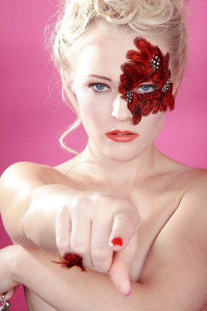 beautiful face with red feather and shows to you photo