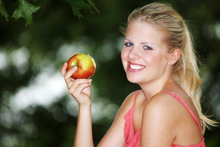 pretty blonde model eating an apple photo