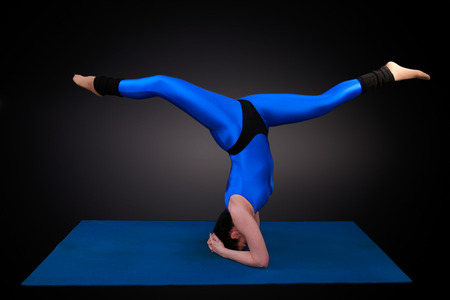 headstand: yoga woman shows a headstand spagat