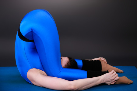 closed club: yoga woman shows the knee-ear position