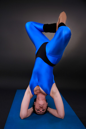 headstand: yoga woman shows a headstand triangle with rotation