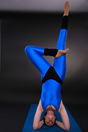 headstand: yoga woman showing a live tree headstand