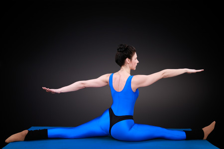 yoga woman shows the position balancing act from behind photo