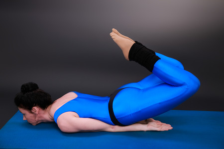 closed club: yoga woman shows the position grasshopper bent