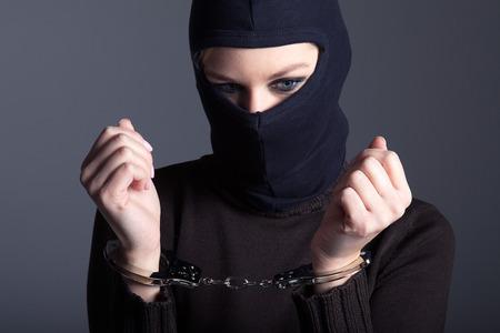 Einbrecher mit Maske und Handschellen