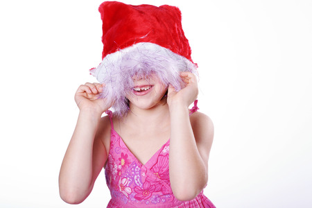 young santa claus girl hiding under hat photo