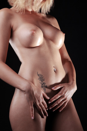 bare breast: Beautiful naked female body on a dark background Stock Photo