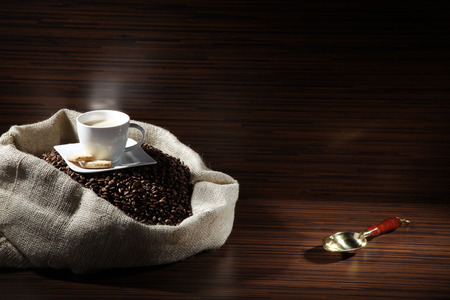 diat product: kaffebohen in a jute bag and cup of coffee
