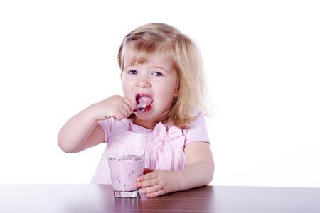 young girl eating a yogurt