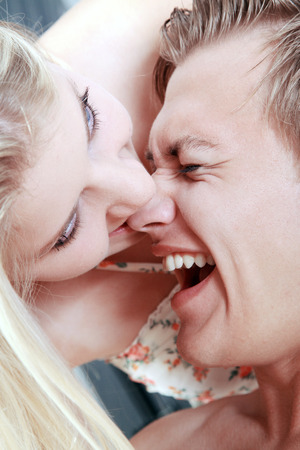 young woman biting playfully in the nose of man photo