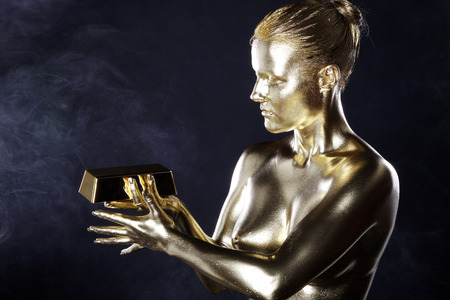 naked gold woman in pose with gold ingot photo
