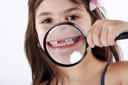 examined: Young girl examined with magnifying glass Stock Photo