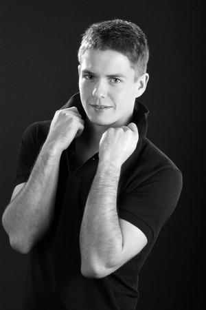 jungen Mann mit den Händen auf dem Kragen als Schwarzweiss-Foto