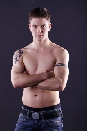 jungen Mann mit freien Oberkörper und Tattoo
