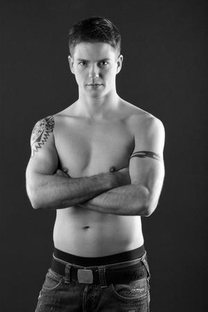 jungen Mann mit freien Oberkörper und Tätowierung als Schwarz-Weiß-Foto Standard-Bild