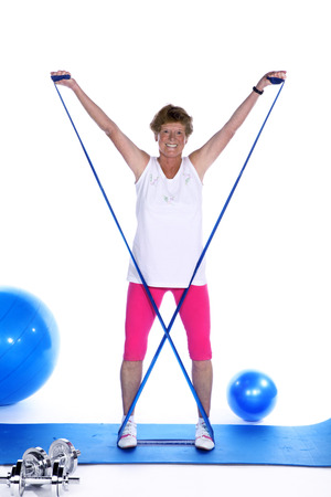 sporty mature woman with stretch band exercises