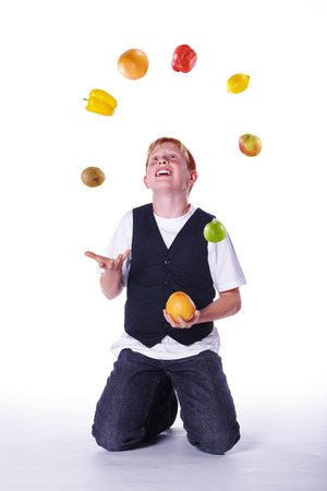 a boy juggling with apples photo