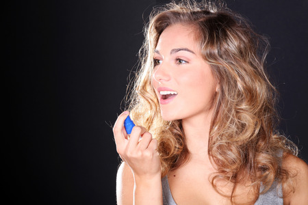 oral care: beautiful woman taking a breath spray Stock Photo