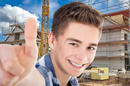 thumps up: construction worker with thumps up and house