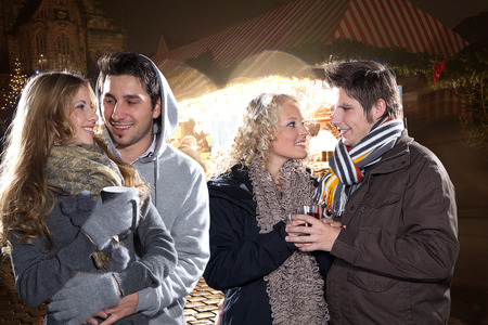 beautiful couple at christmas market and mulled wine