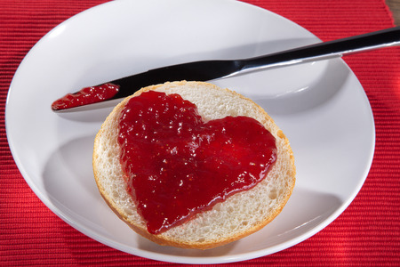 bun with jam with white plate and knife