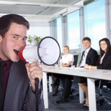 Business man with a megaphone in office