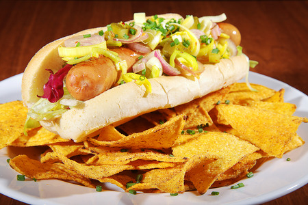 gastro: hot dog with nachos on white plate Stock Photo