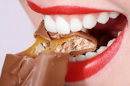 close-up woman model with white teeth and chocolate