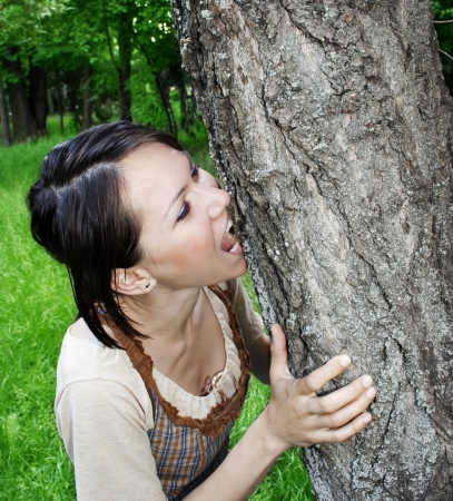 Young woman biting the tree bark photo