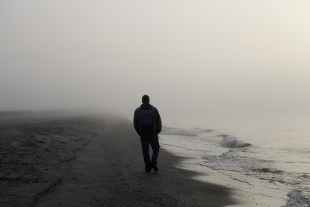 alone in the dark: Hombre solo caminar por una playa brumosa