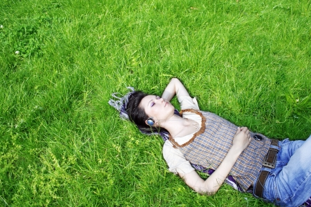 Young woman listening music in the park photo