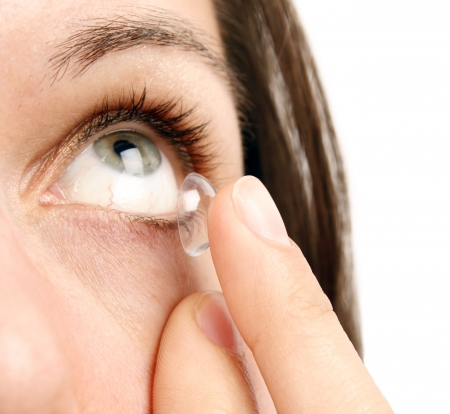 dilated pupils: Woman inserting a contact lens