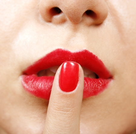 Young woman with her finger on lips photo