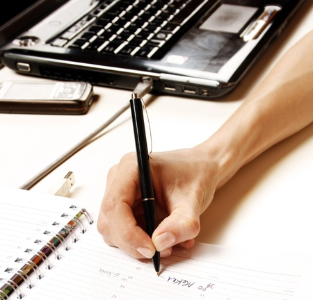 Business woman writing into notebook photo