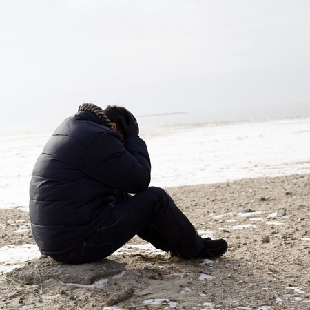 Lonely man sitting on sand in a winter day photo