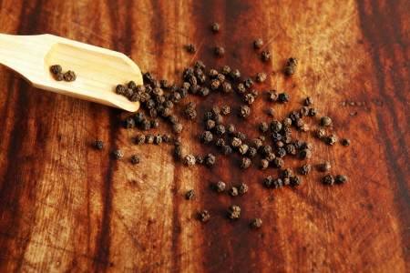 trencher: Pepper grains and wooden spoon on a trencher   Stock Photo