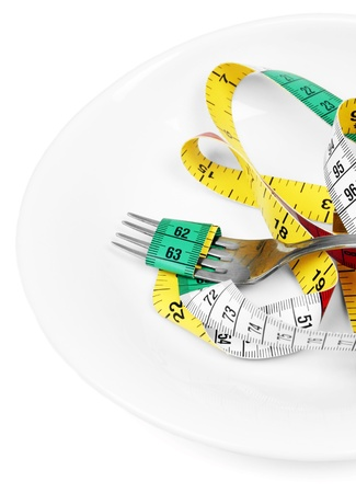 Fork and measuring tape on white plate photo