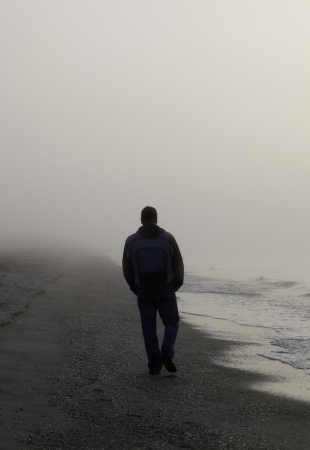 man alone: Lonely man walking on a foggy beach Stock Photo
