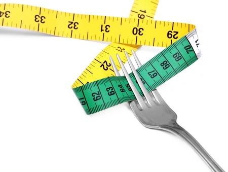 Fork and measuring tape on white background photo