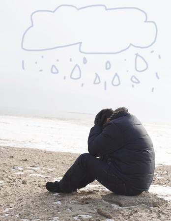 hombre solitario: Hombre solitario que se sienta en la arena en un d�a de invierno Foto de archivo