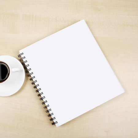 White cup and white page on wooden table photo