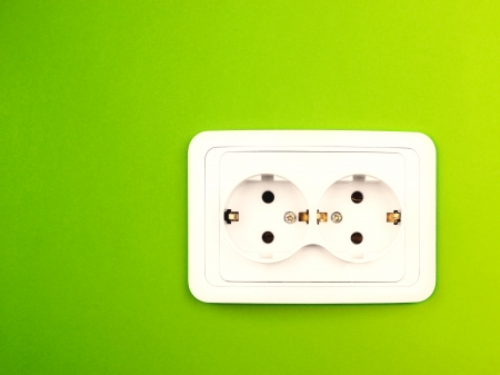 Power outlet on green wall photo