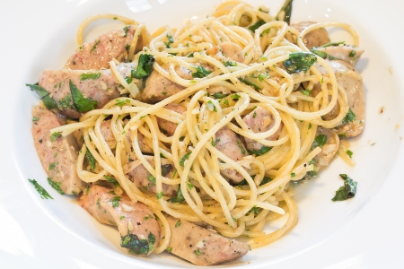 Spaghetti noodles with sausage and herbs on white dish photo