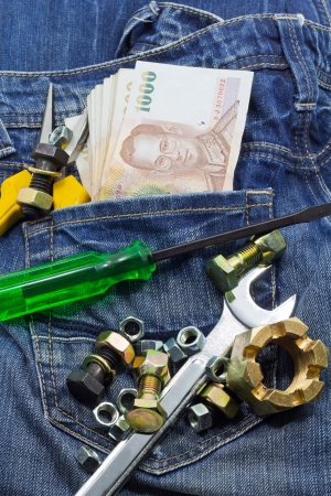 tools and cash on a denim workers pocket
